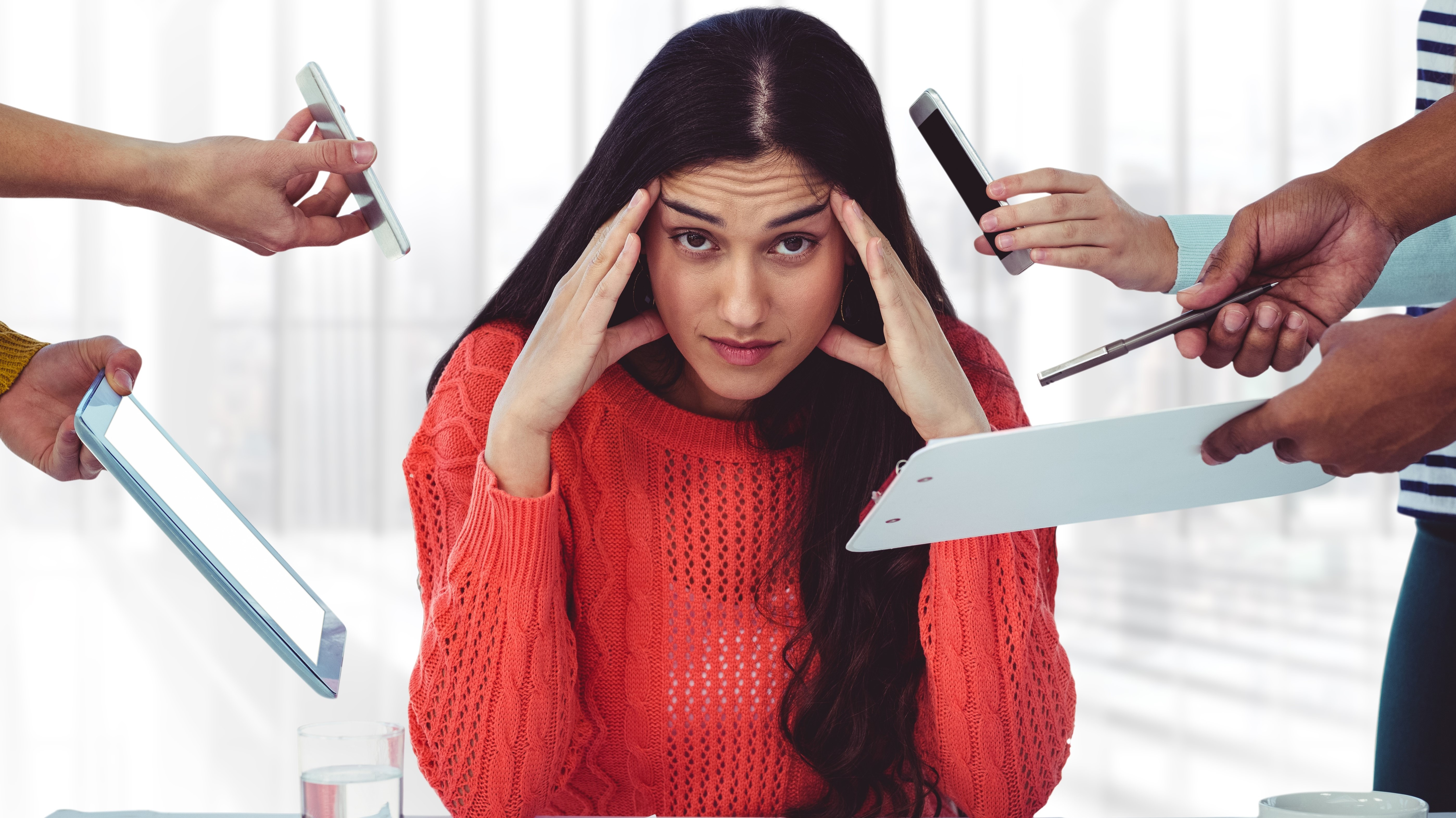 Stresssed Woman Sitting With Hands On Forehead In Office